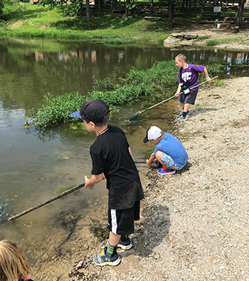 4-H youth at camp cleaning pond