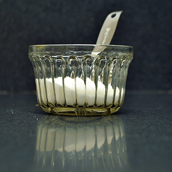 Twelve teaspoons of sugar and a metal teaspoon in glass bowl.