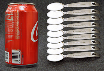 Can of soda and 9 individual teaspoons of sugar.