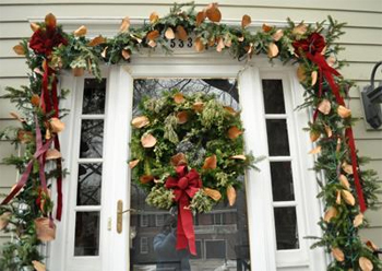 Christmas greenery decorating front entrance of a house