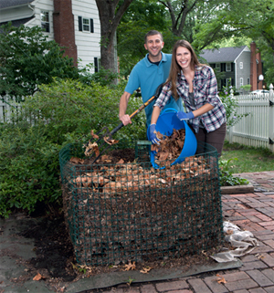 Woman and man building a compost pile